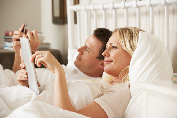 Couple using tablet in bed