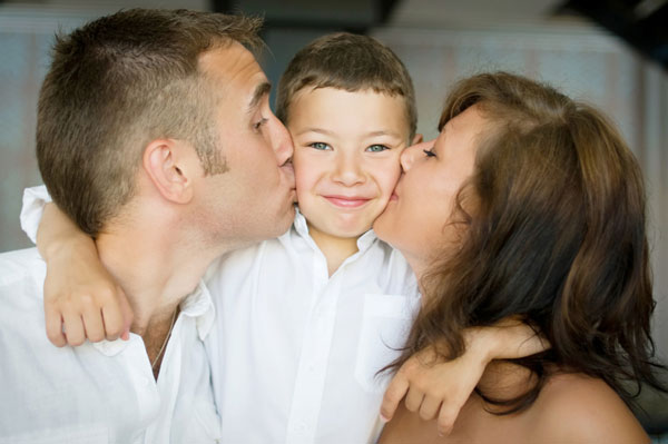 Parents kissing son on wedding day
